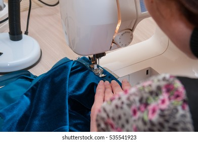 Woman sews lock in a skirt on a sewing machine