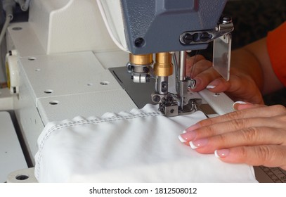 A woman sews on an industrial flat-seam sewing machine. Hands close-up. Soft focus