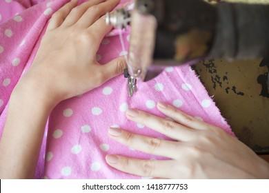 woman sews on a sewing machine
