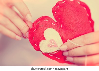 Woman sews red heart shaped toy by needle, body part, conceptual symbol of love and soul pain treatment, happy Valentine day