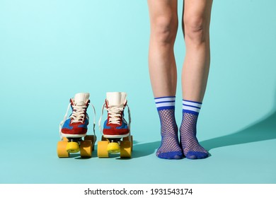Woman in sexy blue fishnet anklets with a pair of colorful roller skates alongside in a frontal close up view of her legs over a blue background with copyspace