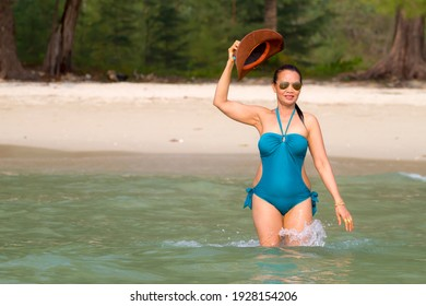 Woman sexy in blue swimsuit walk play at beach Koh Chang Thailand.