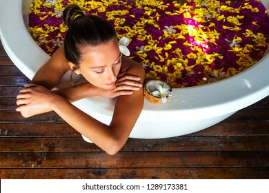 Woman sexy brunette relaxing in bath with tropical flowers outdoor at luxury hotel resort. Organic skin health care. Beautiful girl resting in hotel spa massage and meditation.women's Day March 8