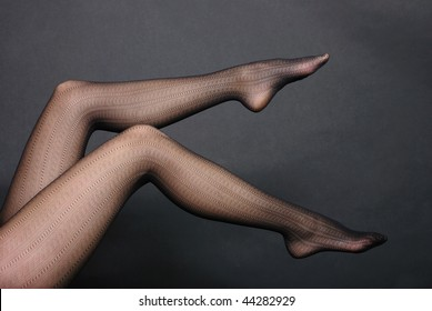 Woman sexy legs in tights on black background