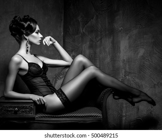 Woman in sexy lingerie and stockings posing in a vintage interior. Beautiful girl in erotic underwear. Black and white.