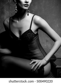 Woman in sexy lingerie and stockings posing in a vintage interior. Close-up of beautiful girl in erotic underwear. Black and white.