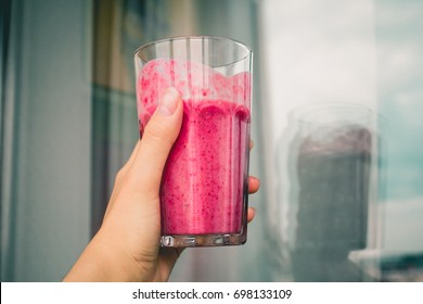 woman or shake hand with drinking pink healthy berry smoothie concept on wall background. vegetarian or healthy food from raspberry. close up or side view.
