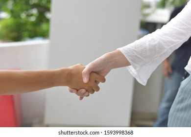 A woman shaking hands with her friend.