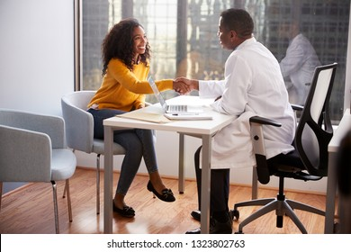 Woman Shaking Hands With Male Doctor In Hospital Office Consultation