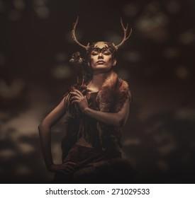 Woman shaman in ritual garment with hawk