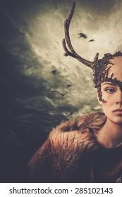 Woman shaman in ritual garment over dramatic stormy sky