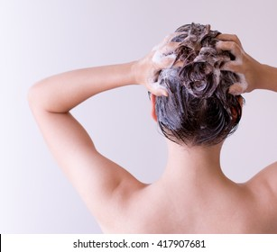 Woman shampooing her hair with both hands on her head in front of a white background.