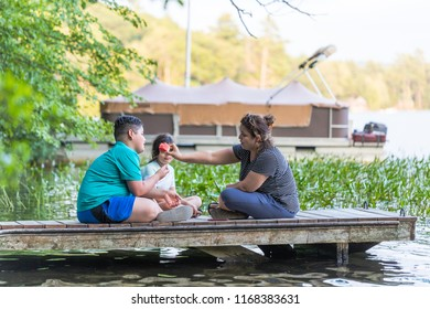 A woman is sharing a piece of watermelon with her son while sitting on a dock