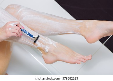The woman shaves with the men's razor of a leg