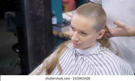 Woman shaving her head baldly. a hairdresser shaves a woman's long hair with a hair clipper.