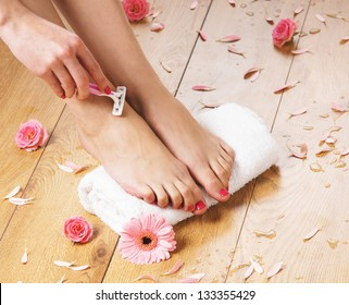 Woman shaving her legs over the spa background