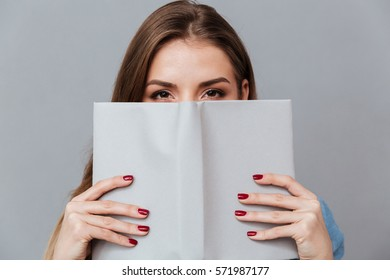 Woman in shirt hiding behind the book in studio. Isolated gray background