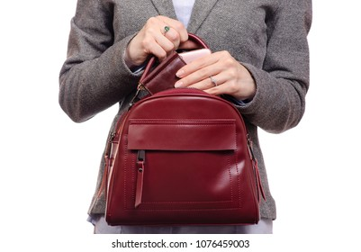 Woman in shirt and jacket put a mobile phone and purse in handbag business on a white background isolated