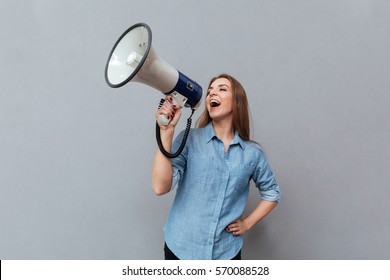 Woman in shirt screaming in megaphone with arm at hip in studio. Isolated gray background