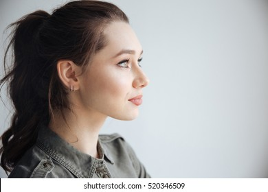 Woman in shirt in studio. in profile. isolated gray background