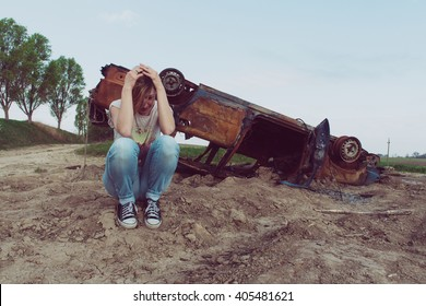 woman shocking after accident, Abandoned rusty burnt car wreck in the background, Car that has been burn right out, even the tires are burnt up