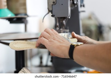 Woman shoemaker sewign flip flops on dedicated machine. Close up crop with selective focus working hands and slipper
