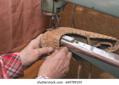Woman shoemaker stitches repairing shoes