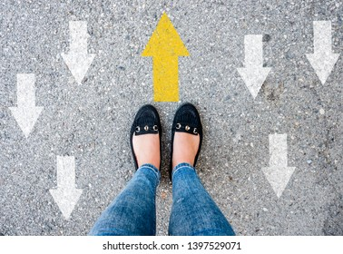 woman shoes on asphalt and opposing direction arrows on asphalt ground, personal perspective footsie concept for finding your own way