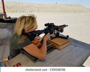Woman shooting Assault Rifle at shooting range