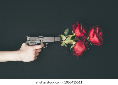 Woman shooting gun with red roses isolated on black