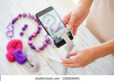Woman shooting her handmade wet felting items on phone camera for advertising