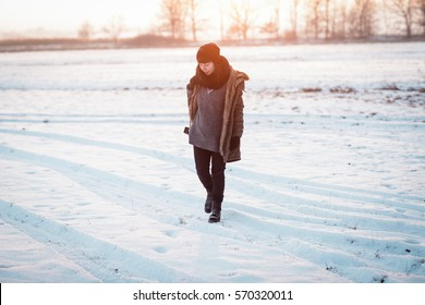 Woman shooting outside in the countryside in the winter on sunset. Color toned image. woman is looking for the best view.Young woman is walking in the meadow.