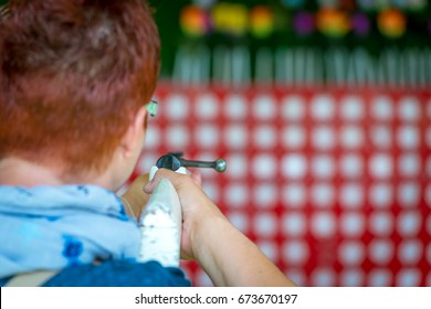 A woman at a shooting range on a funfair