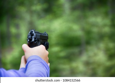 Woman shoots from airgun pistol (black air gun) in forest. Hands and arms visible, different camera angles