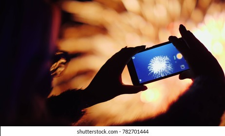 A woman shoots fireworks on a smartphone. The lights are beautifully reflected in her glasses.