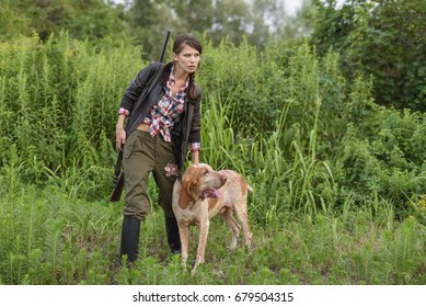 Woman shoots with hunting rifle in a field, hunting reserve in italy with hunting plants and clothing in the company of a hunting dog