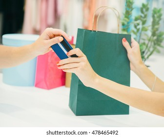 Woman in shop with a credit card in a hand receiving her credit card and shopping bags.Close up.Shopping concept