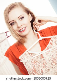 Woman in shop or wardrobe picking clothes from hangers, making perfect elegant summer dress outfit. Fashion and style concept.