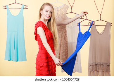 Woman in shop or wardrobe picking clothes from hangers, making perfect outfit. Fashion and style concept.