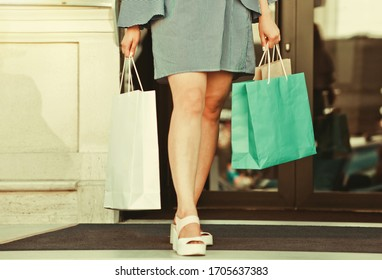 woman shopaholic with triple legs with paper bags for shopping walks around the city. Crop photo