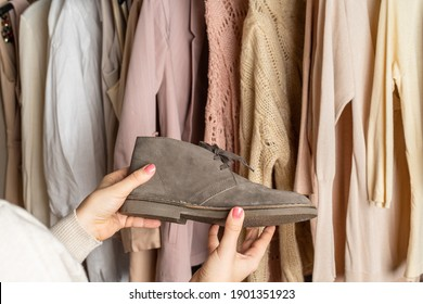 Woman shopper, customer choosing shoes, boots, clothes. Assortment of female clothing, footwear in garment store. Shopping.