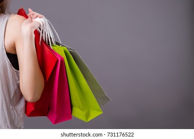 woman shopper shopping, girl shopping or holiday leisure hobby concept, anonymous woman shopper hand holding colorful shopping bag studio isolated, anonymous girl or unknown woman model