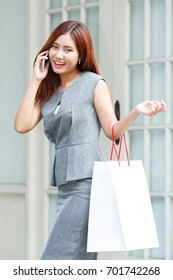 Woman with shopping bag on building background, business concept