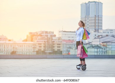Woman with shopping bags, city. Smiling female on gyroscooter.