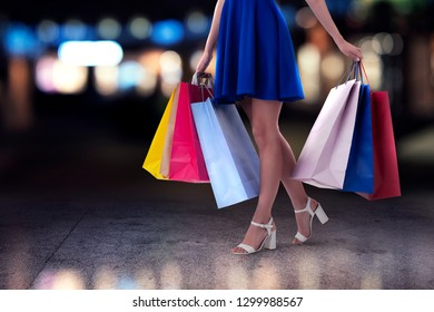 Woman with shopping bags in hand walks in the city
