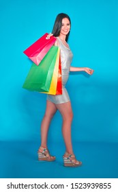 Woman with shopping bags isolated in a chroma key background wearing christmas hat