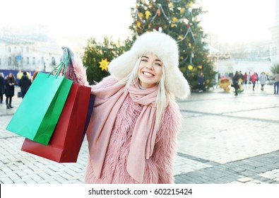 Woman with shopping bags on Christmas tree background