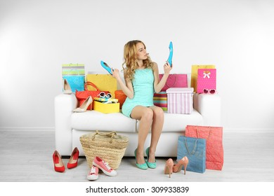 Woman with shopping bags and shoes on sofa in room