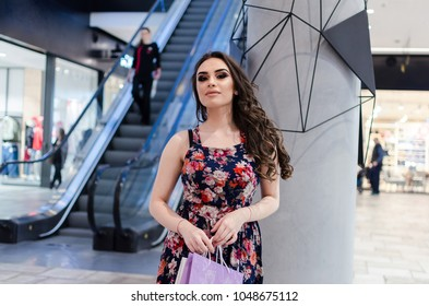 Woman with shopping bags standing in modern bright shopping mall indoor