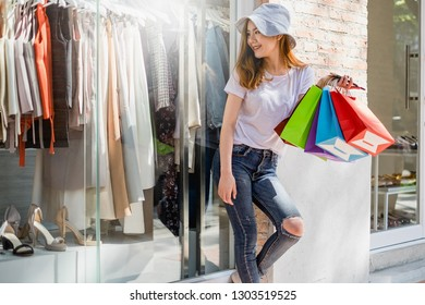 Woman with shopping bags In the summer walking out from shop.